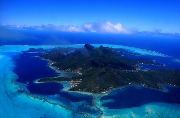 Picture taked from the Air Tahiti flight from Moorea to Bora Bora.  Bora Bora is an island in the Leeward group of the Society Islands of French Polynesia, an overseas collectivity of France in the Pacific Ocean. The island, located about 230 kilometres (140 mi) northwest of Papeete, is surrounded by a lagoon and a barrier reef. In the center of the island are the remnants of an extinct volcano rising to two peaks, Mount Pahia and Mount Otemanu, the highest point at 727 metres (2,385 ft)…