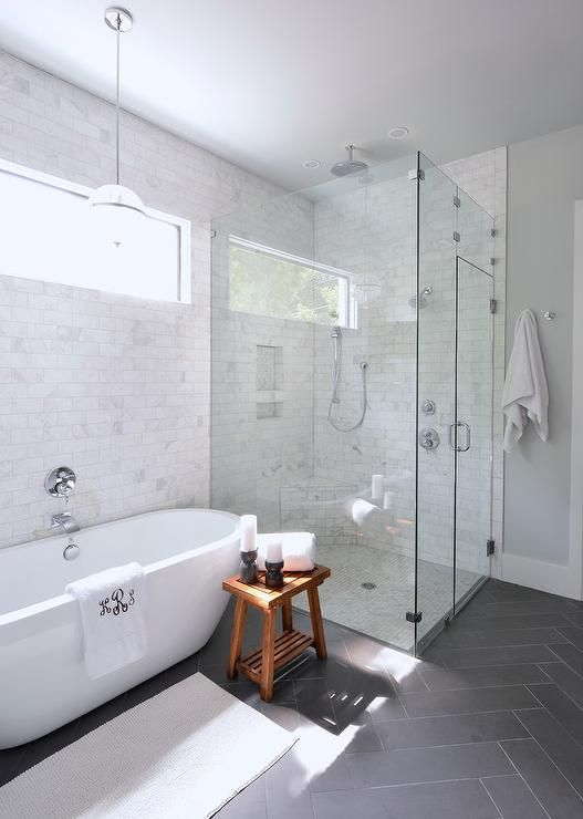 white bathroom free standing tub monogrammed towel grey floor tile glass shower pendant lighting above tub lilli design