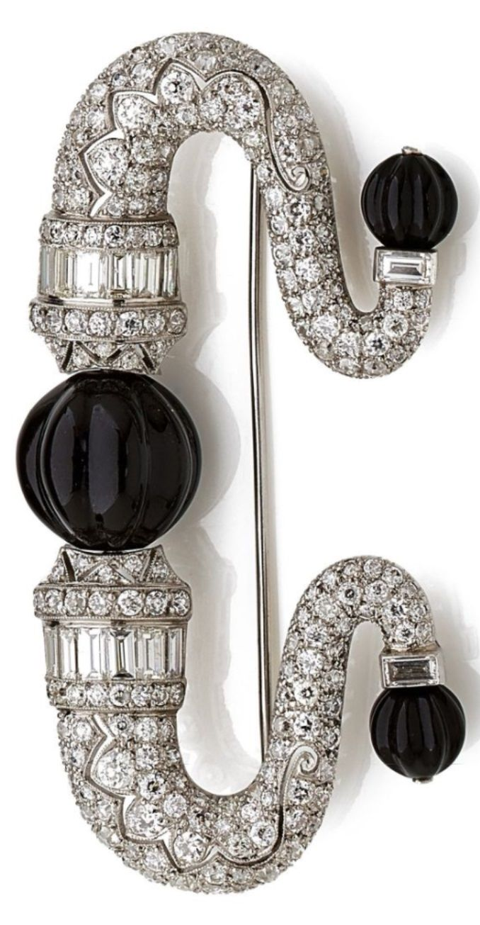 An Art Deco diamond, onyx, platinum and 18k white gold brooch, circa 1930. The stylised fibula set with brilliant-cut and baguette diamonds, and set to the centre and each terminal with onyx spheres, mounted in platinum and 18k white gold. Length 7 cm. #ArtDeco #brooch