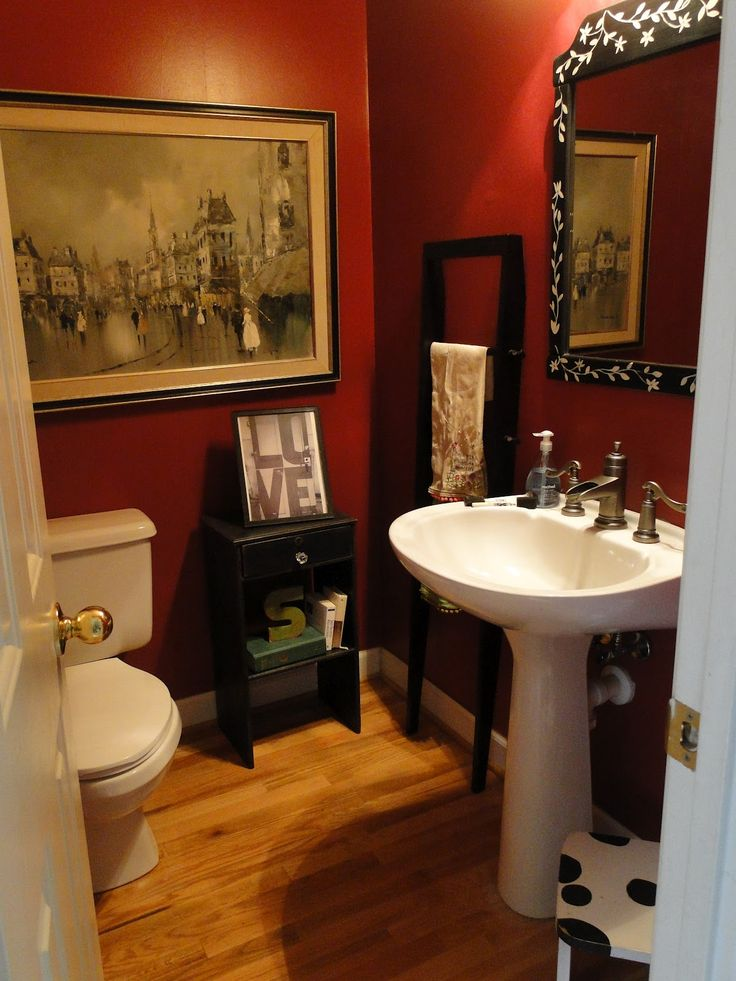 artwork canvas portray on red wall painted color with white pedestal washbasin plus varnished wooden floor for guest bathroom ideas with sink vanities plus