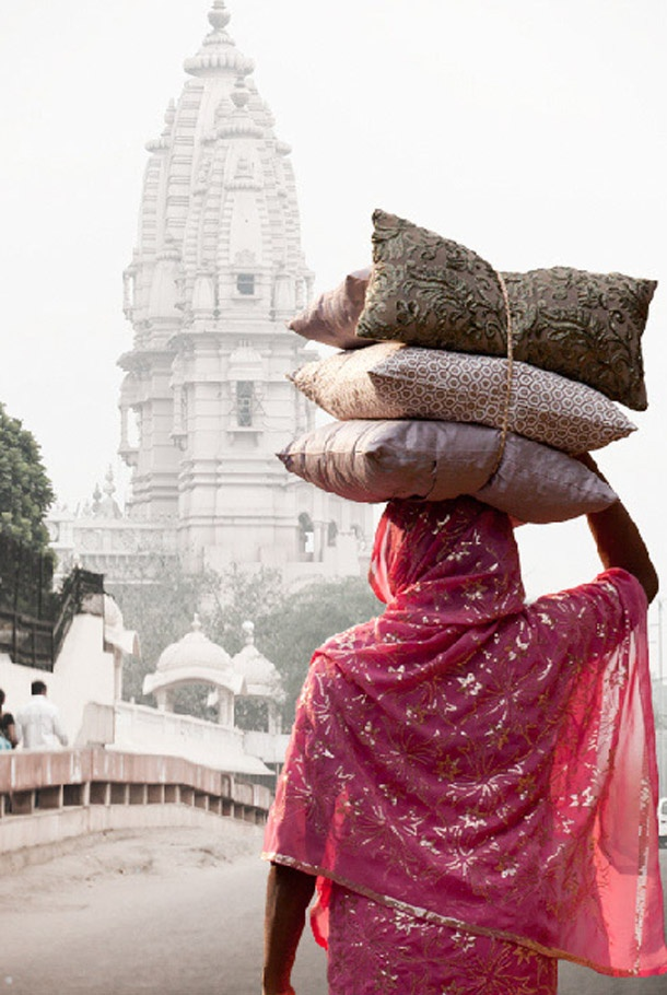 Temple in the back ground, a woman in a pink sari and her load.