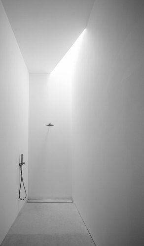 Minimalist walk-in shower with skylight.