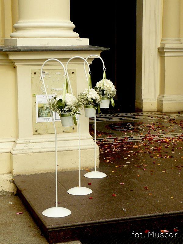 białe stojaczki z kwiatami przed wejściem do kościoła w Wilanowie