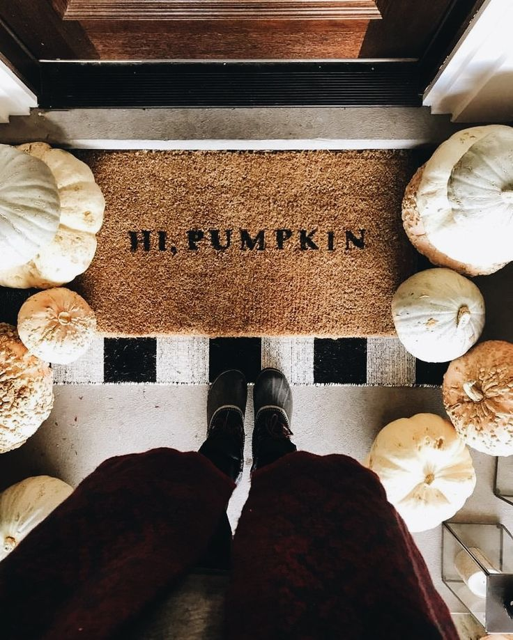 """Hi, Pumpkin"" welcome mat at the door with white pumpkins, warm fuzzy coat, and winter duck boots"