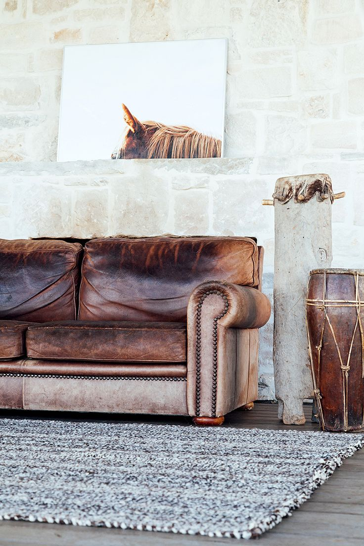Distressed leather couch and horse art. Great living room space.