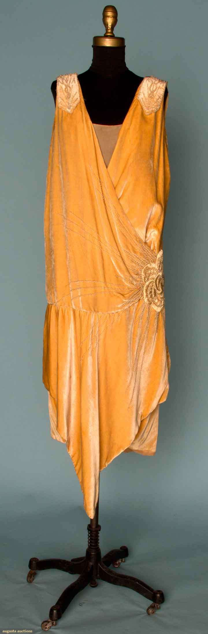 Mid-1920s Beaded velvet flapper dress: faun silk velvet, large Deco rose embroidered over left hip in silk floss and pearl beads, pearl bands descend from shoulder to low back neckline and tie over CB, a-symmetrical hem flounce, and silk lining.  Via Augusta Auctions.
