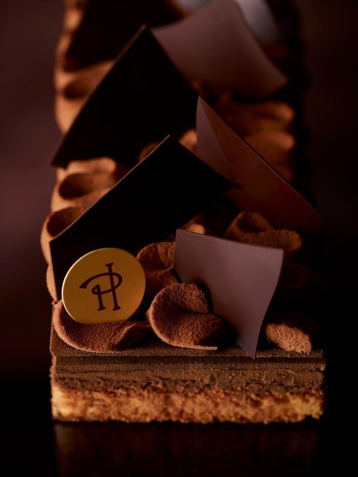 Pierre Hermé. Les amoureux du chocolat vont tomber dans une embuscade définitive. C'est cette toute dernière création de Pierre Hermé, dangereusement transgressive. Du chocolat dans tous ses états, un jeu sur les textures immense. Praliné feuilleté, croustillant, chocolat noir, craquant, ganache chocolat, fondant, fines feuilles noires, croquant, biscuit amandes, moelleux. Le chocolat Pure Origine Madagascar, Plantation Millot a son apogée.