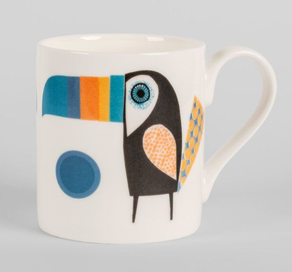 A delicious colourful toucan in blues and yellows proudly perches on a bone china mug.Perfect for tea and bird lovers , or even for birds that love