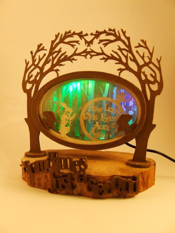 Alice in wonderland lamp made of green wood filament and acacia. The four-layer shadow box is illuminated in green.  The lamp is, as the fairy tale, a little rough around the edges. The most natural-looking appearance has been chosen for this beautyfull handmade light.  Height 30 centimeters Width 20 cm  USB power supply (5 V) or battery (3 x AA)