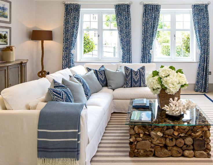 This driftwood coffee table with glass top acts as a stunning statement piece in our Millgate living room design, adding an organic, earthy element, warmed by these charming blue Designers Guild fabric cushions.