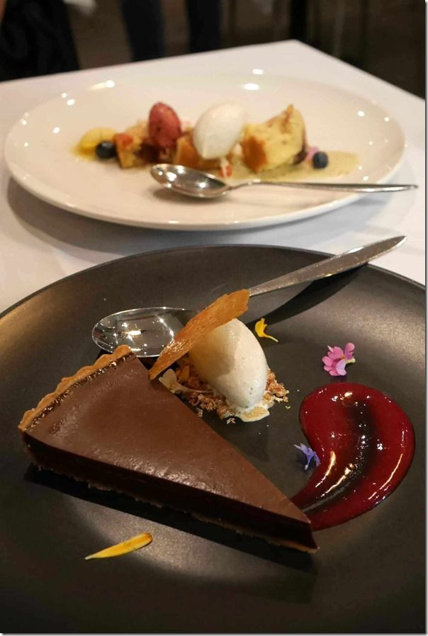 A chocolate tart is luxurious and silky smooth, served with rich hazelnut praline and a tart raspberry sauce.