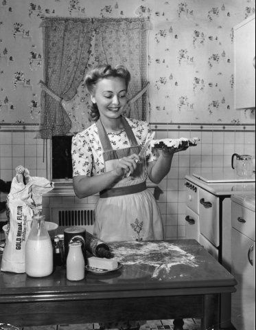 Woman making pie in the vintage kitchen, 1940s