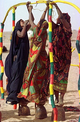 Tuareg women, recently returned refugees, build a tent in Tin Shabane, Mali, in early March 1997. A year after an armistice ended a free-for-all war in Mali, more than 80,000 Tuaregs have returned from Mauritania, Libya, Algeria, and Niger, but most are too poor to resume their 1,000-year-old way of life as nomad cattle herders