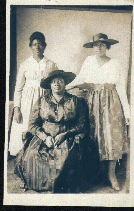 Of Another Fashion — This portrait (ca. 1913) was taken at Palmer's Photography Studio, a Black-owned business in Galveston, Texas. Standing are Dora Dolly Sanders (L) and Johnnie Mae Dolly ®, daughters of Rita Dolly (seated). I don't know much about the clothing except that Rita (my great grandmother) and Johnnie Mae are wearing taffeta while Dora's dress is made of cotton. Johnnie Mae was known for being very stylish in her younger years (as you can see from the boots and hat) while Dora…