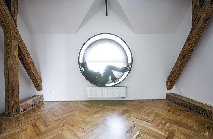 Do uličního štítu střešního vikýře navrhli architekti kruhové okno s nerezovou balotinovanou šambránou, které slouží i k posezení a odpočinku.