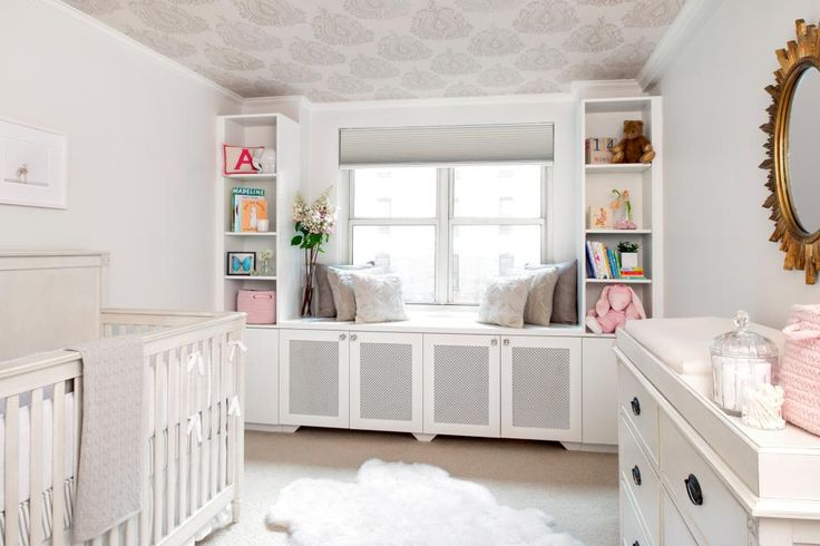 This sweet, neutral nursery is filled with softness and light. Walls in Benjamin Moore's Dove Wing give way to a subtly patterned Romo wallpaper used on the ceiling for added impact. Built-in shelves and cabinets offer plenty of storage for baby items and toys, and a sheepskin rug provides comfort underfoot.
