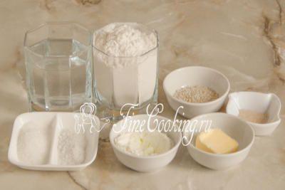 Шаг 1. В рецепт булочек для гамбургеров входят следующие ингредиенты: пшеничная мука высшего сорта, вода, быстродействующие дрожжи, сахарный песок, соль, сухое молоко, белый кунжут и сливочное масло