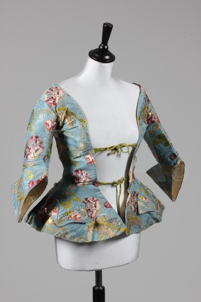 Here is another from KTA up for auction.     Item Description: A fine sky blue brocaded silk caraco jacket, circa 1740-45, with winged cuffs, short peplum skirt with two faux pockets, green ribbon ties to the front, the silk, probably Spitalfield with gold and silver leaf scrolls Snowshill Manor includes a similar caraco jacket in bright red brocaded silk with winged cuffs which is dated 1735-40.
