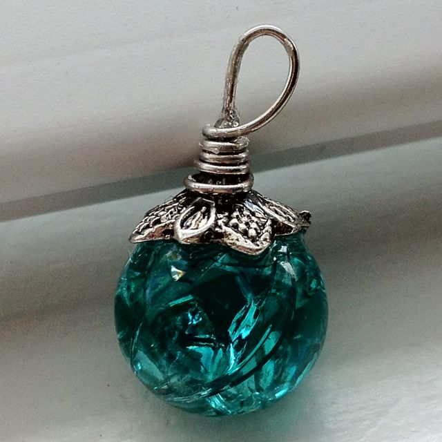 Necklace charm I made (Pinterest inspired)! Bake a marble at 350 for 20 minutes, then dump them in ice water. The inside cracks but the outside stays intact! For the top I used E-6000 glue with a head pin to make the loop and a bead cap over the base of the pin. Voila! :)