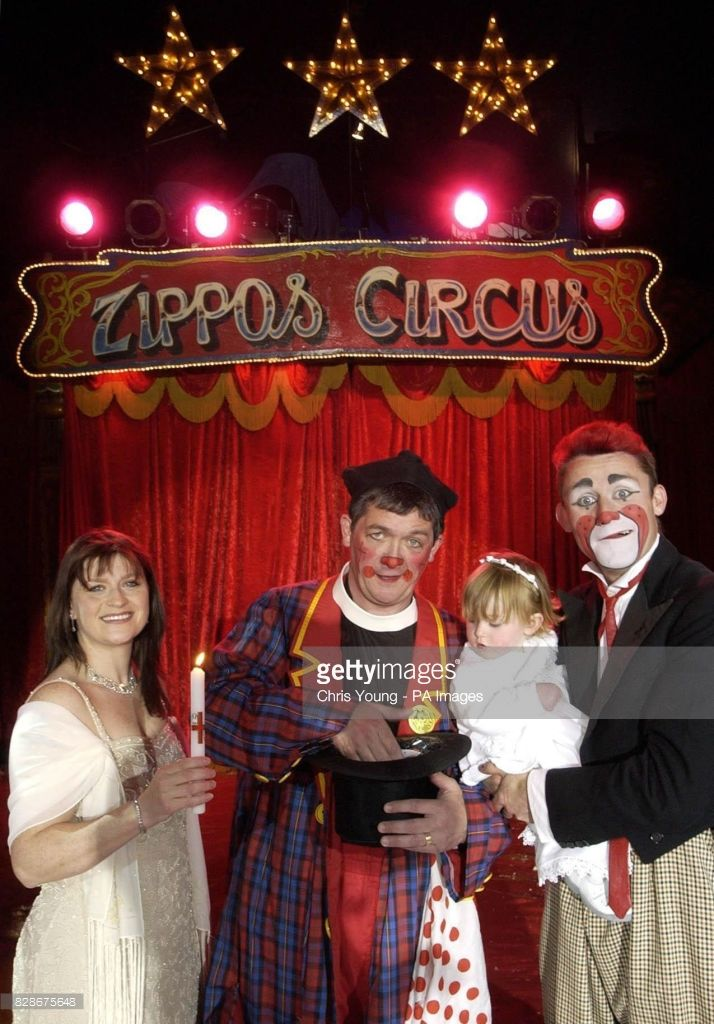 Willow, the eighteen month old daughter of Zippo Circus clown Tweedy (right) and his wife Sharon (left), inspect the font fashioned out of a top hat, held by Rev Roly Bain, an ordained priest who ministers through clowning, under the circus Big Top in South London. * Willow is believed to be one of the first children in the UK to be baptised by a circus clown,