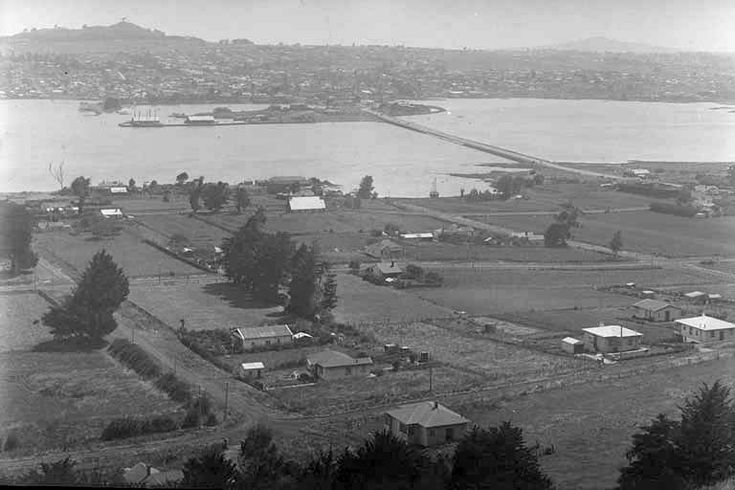 1931. Looking north from Mangere Mountain across the Manukau Harbour towards One Tree Hill and Onehunga (centre background) showing Mangere Bridge, continuing as Coronation Road, Taylor Road (left to right immediate foreground), then McIntyre Road (left to right across centre), Church Road (left to right across upper centre), Scott Avenue (diagonal left), Woodward Avenue (diagonal right of centre) and St James Church (centre). Sir George Grey Special Collections, Auckland Libraries, 4-4744.