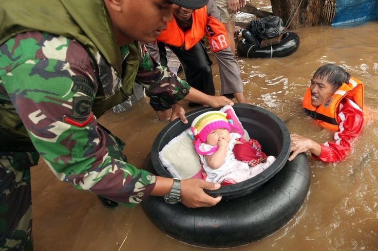 JAKARTA FLOODS: Rescuers evacuated a baby from a flooded area in Jakarta, Indonesia, Friday, as the death toll climbed from severe flooding. Drownings, landslides and flood-related electrocutions have killed at least 11 people, the National Disaster Mitigation Agency said on January 18, 2013 | © Adi Weda | European Pressphoto Agency