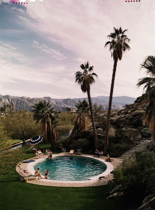 A wealthy group of young people relax by a pool in California,...