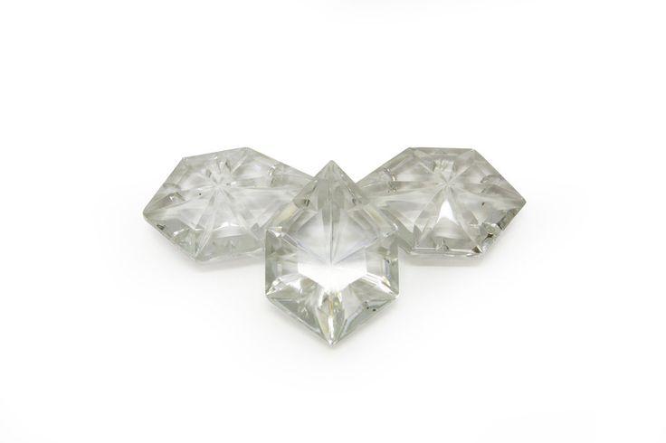 € 4,95 - Kroonluchter kraalwerk. helder glazen kraal in de vorm van een zeshoek. Voorkant van de kraal heeft een 6-hoekig vlakje. De achterkant is in een puntje gevormd dit maakt dat je een 'schitterende' lichtval krijgt,