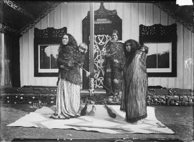 Maori women with babies on their backs standing in front of a meeting house