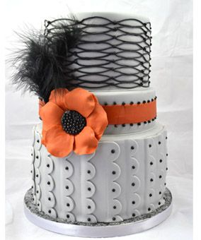 Beads and feather wedding cake. grey black and orange wedding cake with black oval laced effect and vertical scalloped edge with beading finish. Anemone flower wedding cake