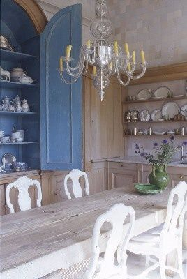 French country traditional dining room in blue and white. Love the open shelving full of ceramics and wooden table with white chairs.