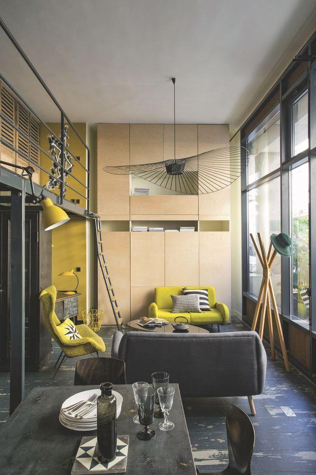 Le salon face à la baie vitrée avec son canapé jaune