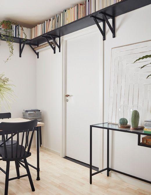 Korkealla katonrajassa huonetta kiertävät kirjahyllyt.