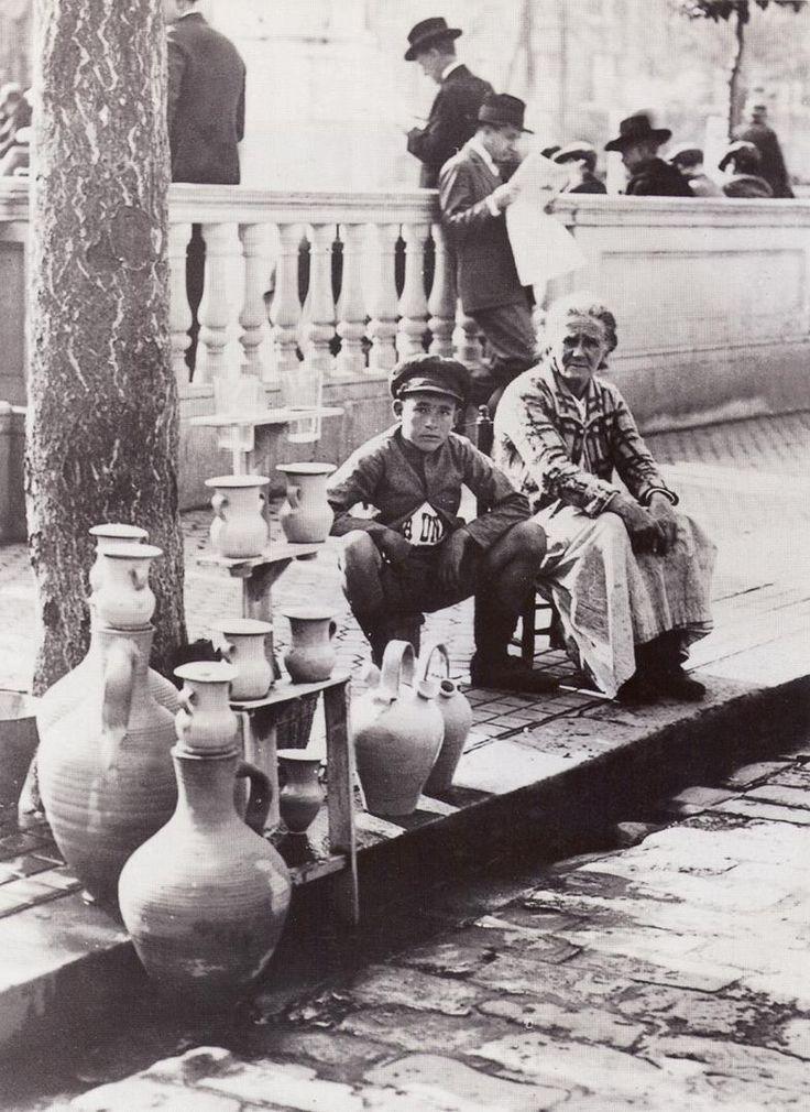 """Aguador en Madrid - Los vendedores ambulantes, muchos de ellos chiquillos o mozas de cántaro, que iban por la ciudad voceando su mercancía, """"¡agua fresca!"""", con una pequeña cesta y uno o más vasos o jarrillos. Estos últimos eran muy populares en las procesiones religiosas o actos públicos diversos. Más tarde se introdujo la costumbre de servir el agua acompañada de unas gotas de anís, limón, azucarillos, canela y otros sabores atractivos"""