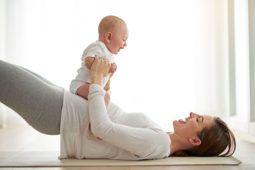 mulher deitada segurando seu bebê