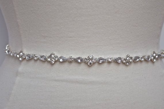 Gorgeous ultra thin crystal rhinestone trim with clear round stones and a very light gray pear shaped stone (very subtle and gives it an extra bit of sparkle) in a silver setting. Approx 1/4 in width.  Available in 4 sizes:   - 12 Trim with 36 of ribbon- Most commonly used as a hair band or a flower girl sash  - 12 Trim with 60 if ribbon - Only extends the very front of waist  - 18 Trim with 60 of ribbon- Base on waist size, trim will wrap from side seam to side seam of your dress. - 24 Trim…