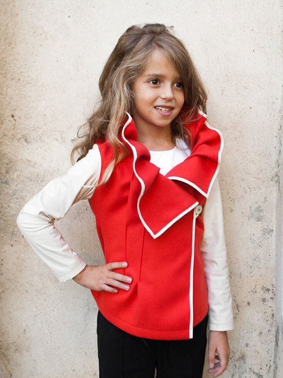 This asymmetric wool blended girls jacket with fuax leather long sleeves has interesting pleated and original designer shape collar. Contrast faux leather piping follow collars shape. Asymmetrical stitches shape the fitted silhouette of the girls wool blend jacket. It fasten with 1 button on the front panel.    Our wool blend collar jackets are in sizes for 2 3 4 5 6 7 8 9 and 10 years old girls.    Your little toddler girl princess will looks stunning with this special occasion jacket, and…