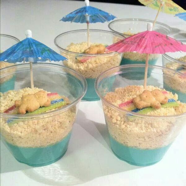 Blue pudding or blue jello, crushed vanilla cookies or vanilla oreos, sour straws for beach towel & teddy grahams. Top off with lil umbrella