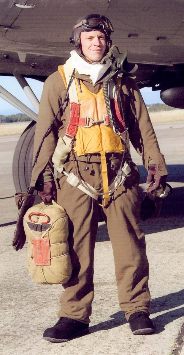 This is a typical flight suit that was typical during WWII. He is prepared with a helmet, respirator mask, and even a life jacket.