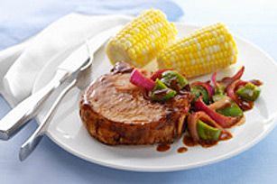 4 center-cut bone-in pork chops (1 lb.)  1 tsp. oil  1 onion, sliced  1 green pepper, cut into strips  1/2 cup KRAFT Honey Barbecue Sauce