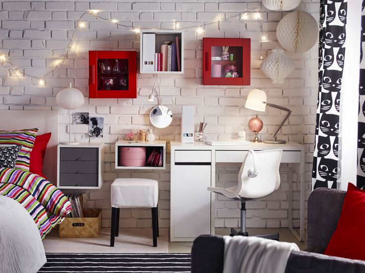 A bedroom furnished with a white desk and swivel chair combined with red and white wall cabinets.