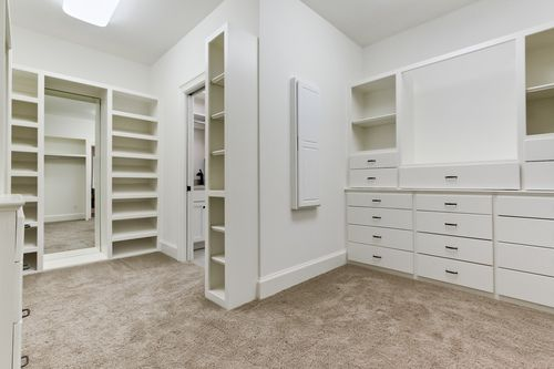 Master closet with custom shelving off of the connected laundry room. Designed and built by Ramage Company.