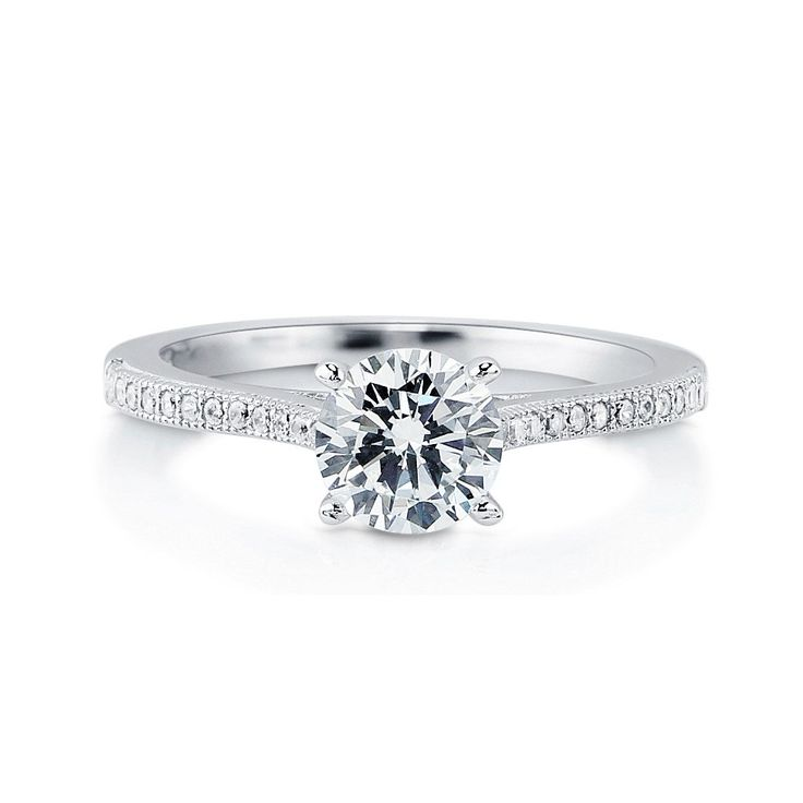 This solitaire with side stones ring is made of rhodium plated fine 925 sterling silver. Band measures 2mm in width. Features 1.28 carat round cut cubic zirconia (7mm) in 4-prong setting. Accented with 0.18 ct.tw round cut cubic zirconia in bezel and micro pave setting. Nickel free.