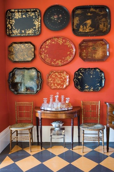 The wonderful red wall is the perfect background for this collection of trays. This is a great way to add art inexpensively. House & Home