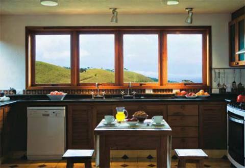 Além de contribuir para a integração com a paisagem, as grandes janelas de vidro da cozinha aquecem o ambiente no inverno.