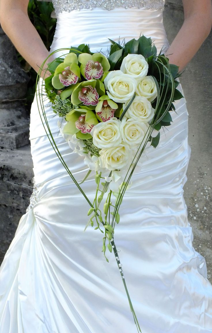 Wonderfully different heart shaped bouquet with green cymbidium orchids and ivory roses.
