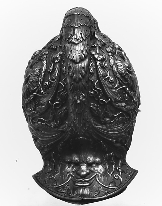 Filippo Negroli (Italian, Milan, Circa 1510–1579) - Burgonet (Helmet). Embossed Steel Damascened with Gold. Formed of one plate of Steel and Patinated to look like Bronze, the bowl is raised in high relief with Motifs Inspired by Classical Art. The Graceful Mermaidlike Siren forming the Helmet's Comb holds a Grimacing Head of Medusa by the hair. Back View. Signed. The Metropolitan Museum of Art, New York City, New York.