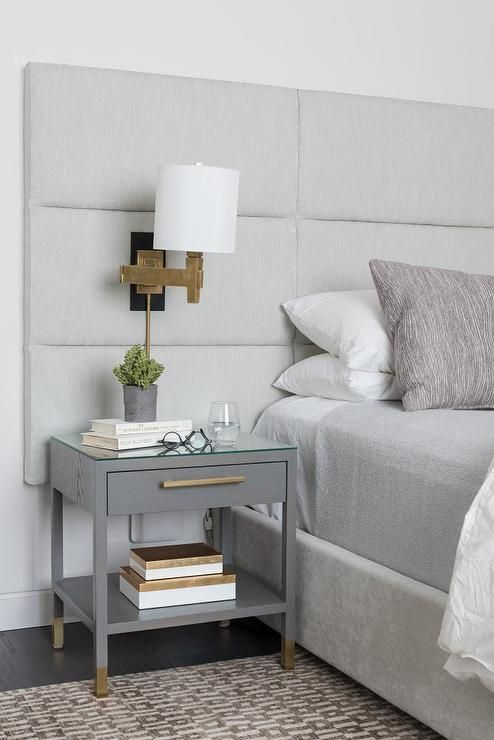A gray channel tufted headboard on bed dressed in white and gray bedding extends over to cover a gray nightstand illuminated by a brass swing-arm sconce.
