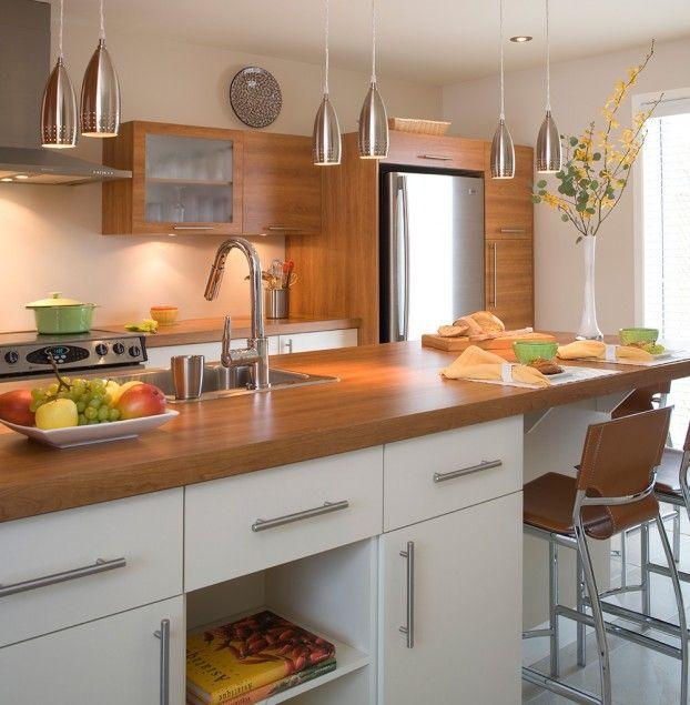 Accueillante et invitante, cette cuisine de type laboratoire est à la fois fonctionnelle et esthétique. L'agencement de deux différentes couleurs de mélamine donne un style actuel à ces armoires. La mélamine au grain de bois horizontal ajoute une touche de chaleur à la cuisine, ce qui rend l'ensemble remarquable. Nous retrouvons la même couleur au niveau du comptoir de stratifié pour couronner l'harmonie des matériaux.