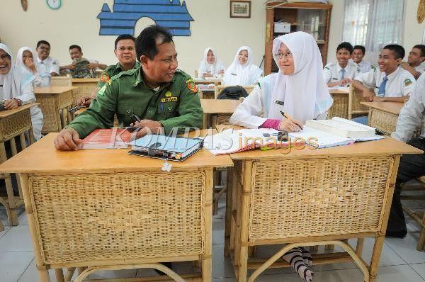 Kepala Dinas Perindustrian dan Perdagangan (Kadisperindag) Aceh, Safwan, berbincang dengan siswa SMA Modal Bangsa yang duduk di bangku sekolah berbahan rotan, Senin (20/1/2014). Disperindag Aceh mengharapkan seluruh mobiler sekolah menggunakan rotan untuk menghidupkan kembali industri rotan di Aceh. Hasil hutan rotan Aceh mencapai 100 hingga 200 ton per bulan